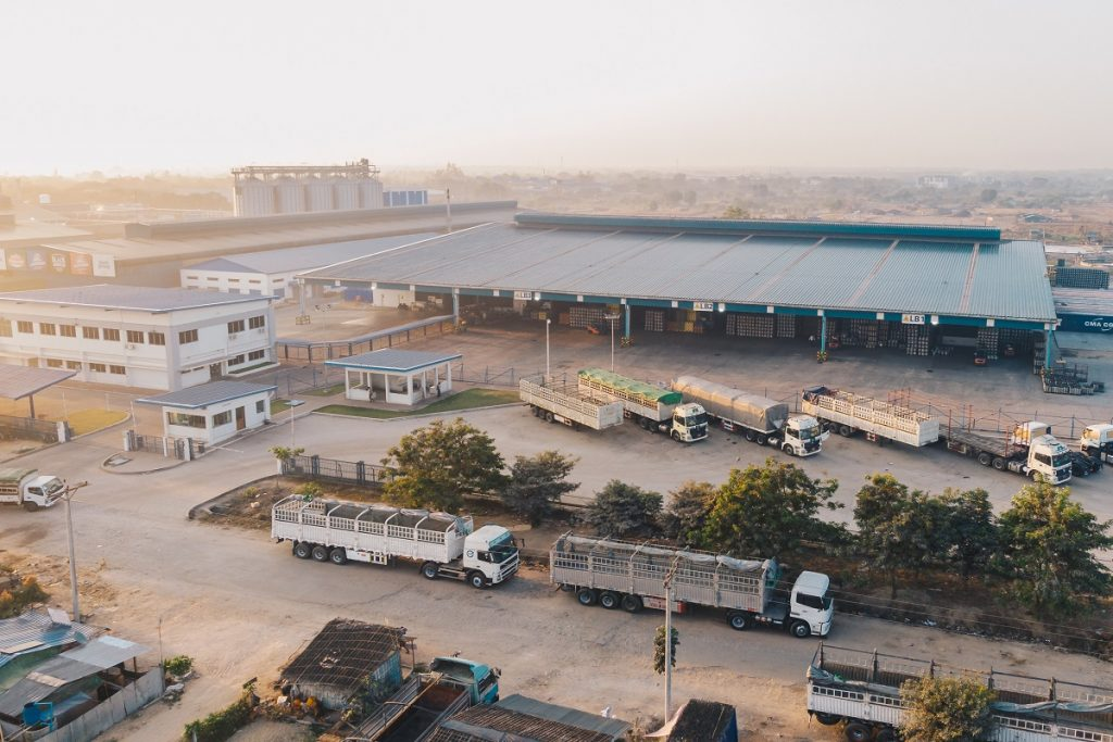 Aerial shot of factory trucks parked near the warehouse at daytime
